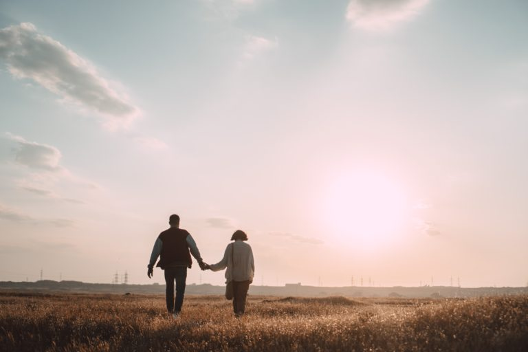 couple holding hands while walking on grass field during daytime